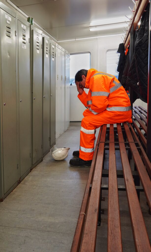 A male worker with mental health, anxiety or grief issues in an industrial environment